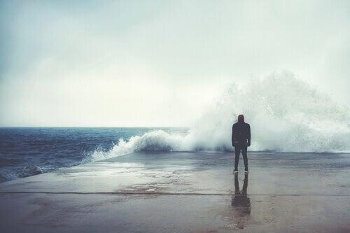 Homem observando ondas quebrando