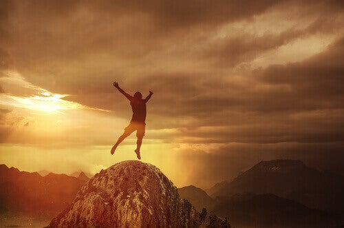 Homem pulando em montanha