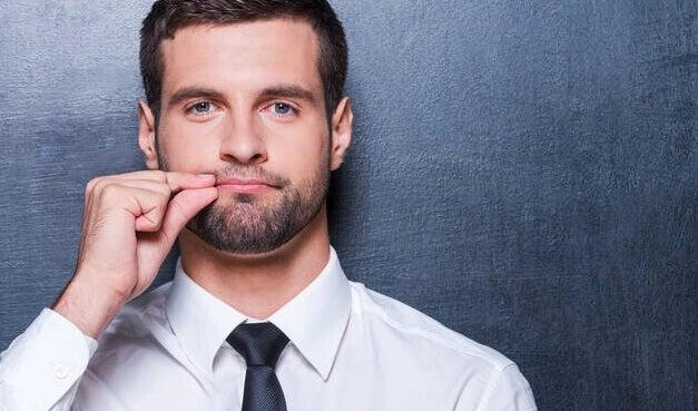 Homem com gesto de boca fechada