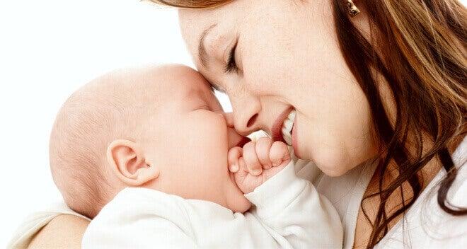 Mulher se aconchegando com seu bebê