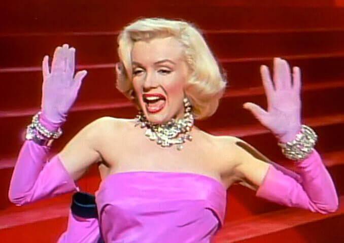 Marilyn Monroe usando vestido e luvas cor-de-rosa