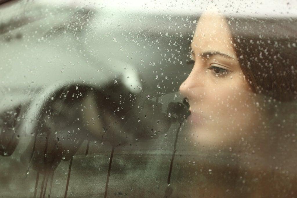 Mulher diante de janela molhada