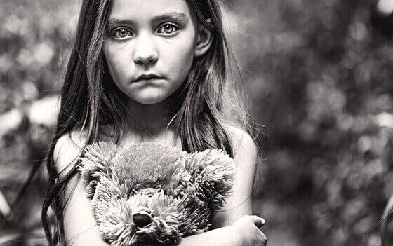 Menina abraçada com ursinho