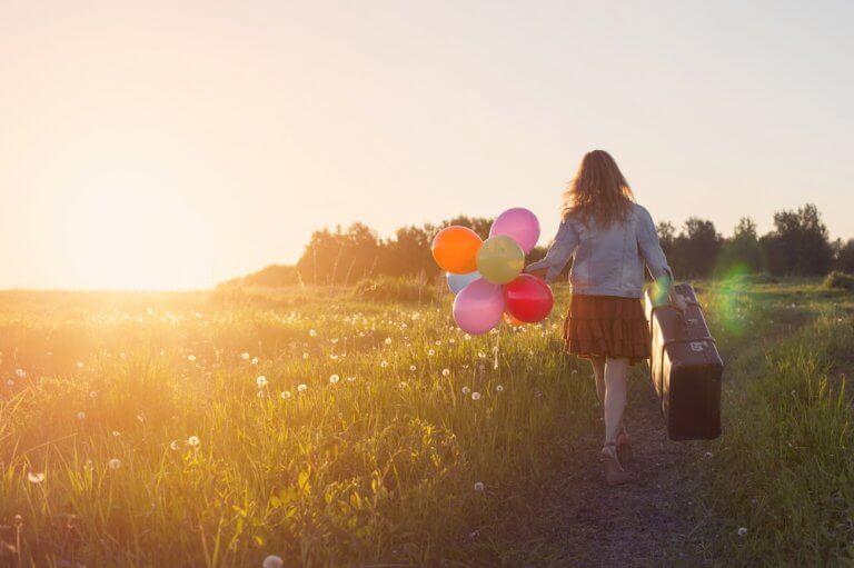 Menina viajando segurando balões coloridos