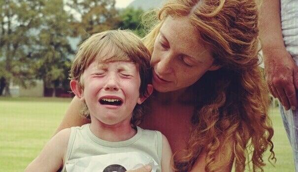 Mãe tentando acalmar filho chorando