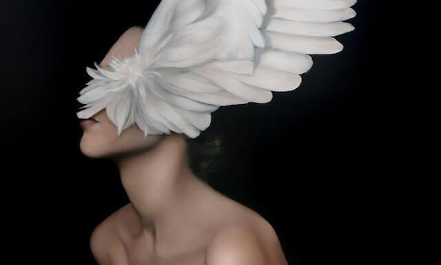 Mulher com asas cobrindo o rosto