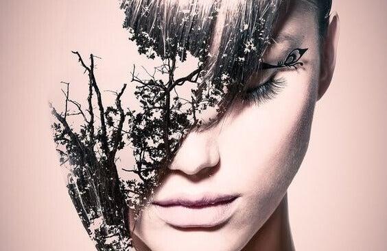 Mulher com galhos de árvore no rosto