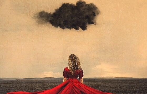 Mulher de vestido vermelho diante de nuvem negra