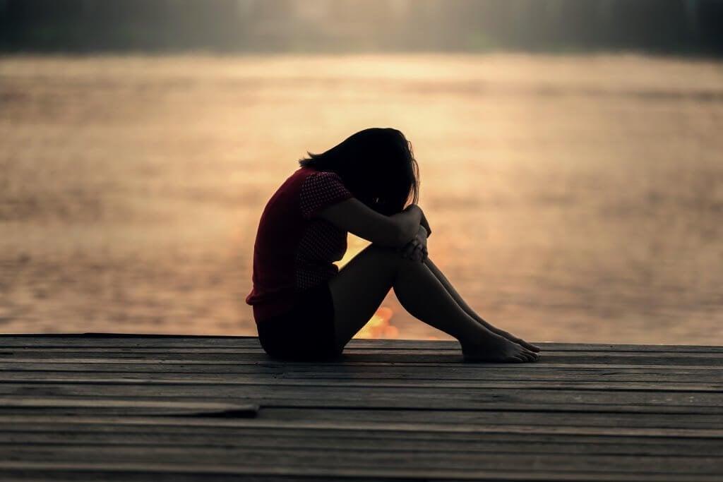 Mulher triste pensando em seus problemas