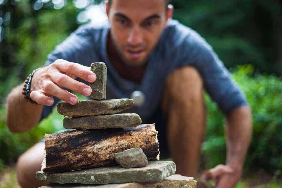 Homem empilhando pedras