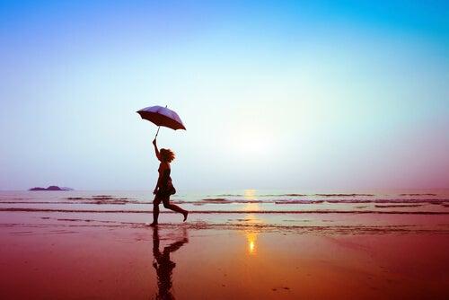 Mulher caminhando em praia com guarda-chuva