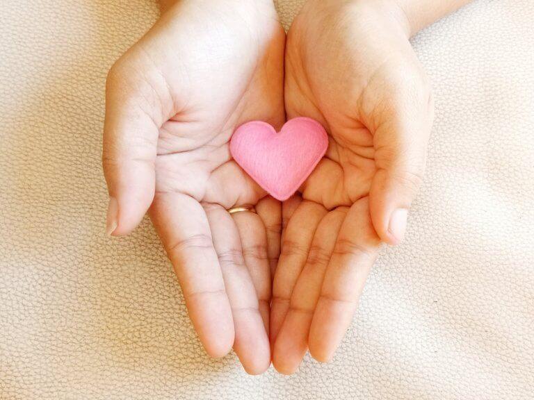Mãos segurando coração cor-de-rosa