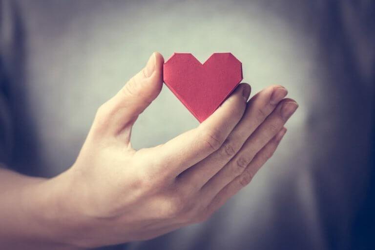 Mão segurando coração de papel
