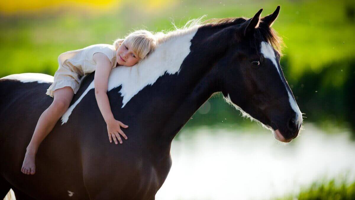 Criança andando a cavalo