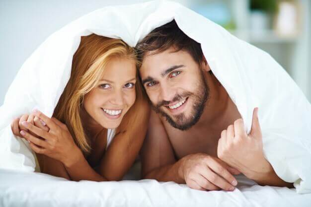 Casal sorrindo sob os lençóis