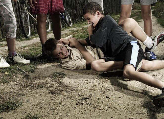 Crianças brigando com outras assistindo