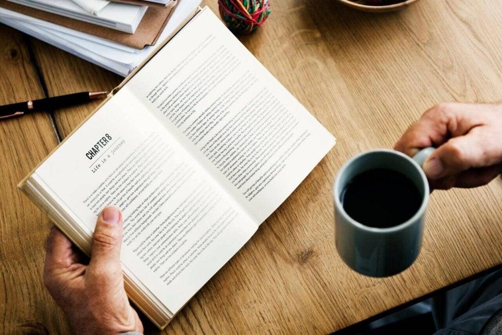 Pessoa lendo livro e tomando café