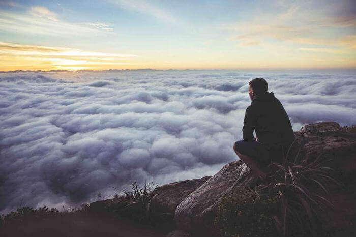 Homem sentado no topo de montanha