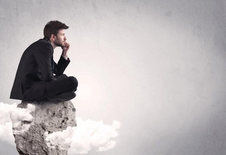 Homem pensativo sentado em pedra