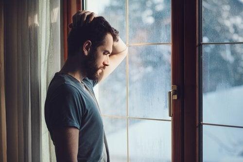 Homem diante de janela