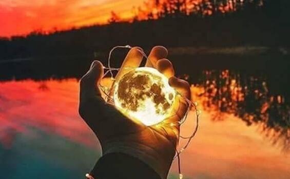 Mão segurando lua brilhante