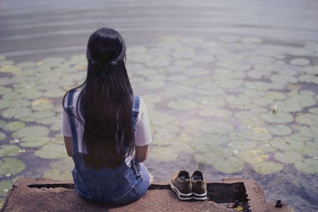 Menina observando lago com plantas