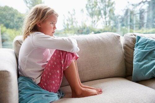 Criança triste sentada em sofá
