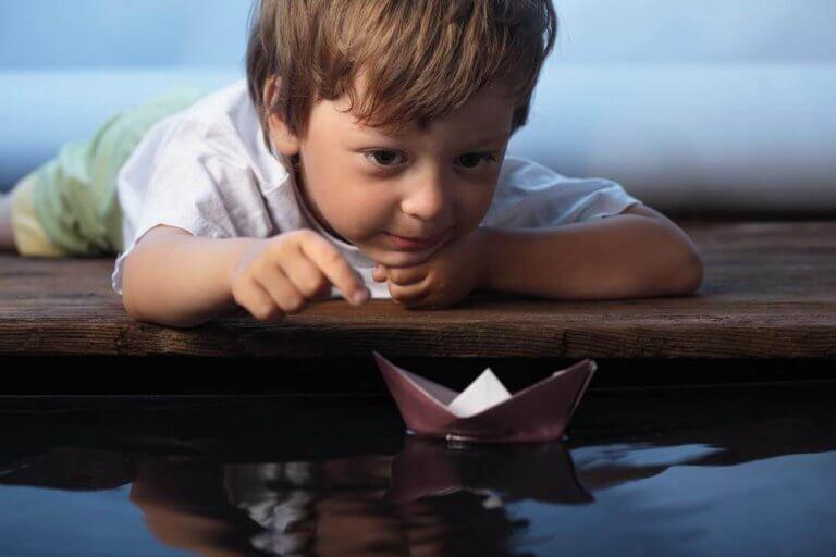 Menino brincando com barquinho de papel