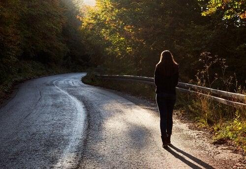 Mulher andando sozinha em estrada