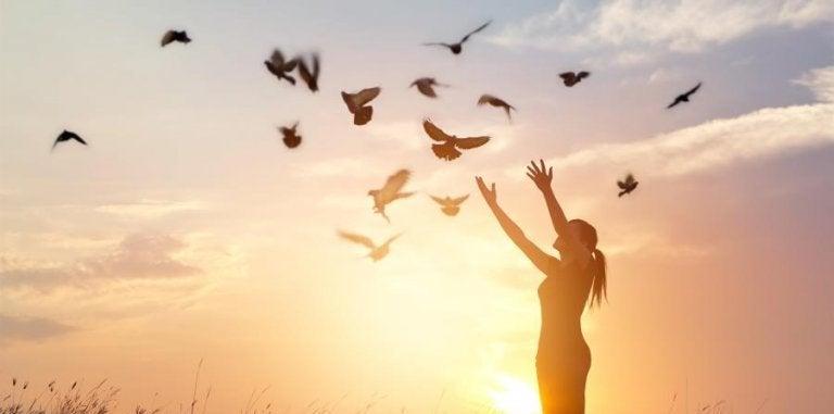 Mulher com pombos voando ao seu redor
