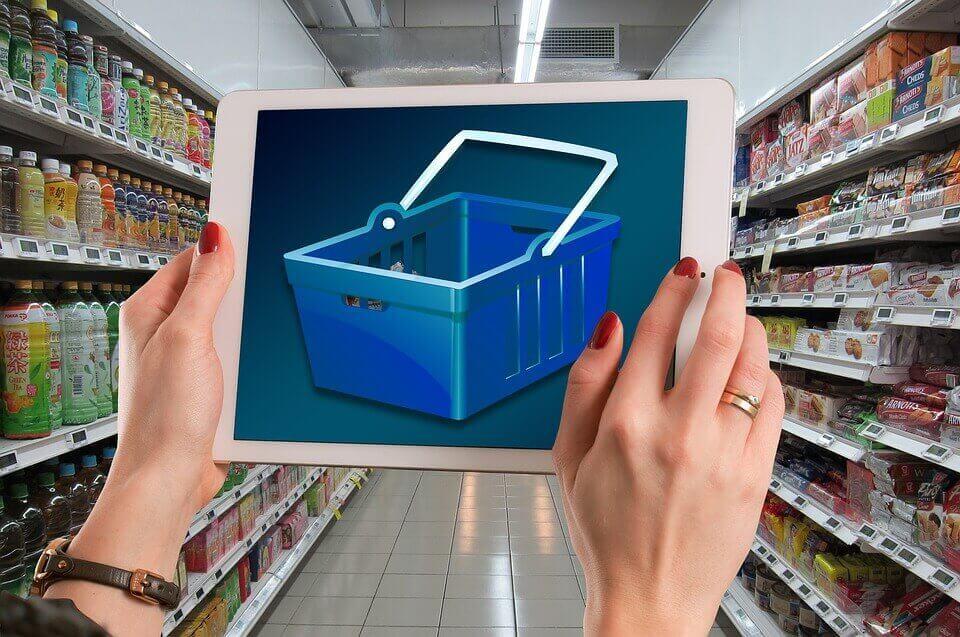 Mulher com tablet com carrinho de supermercado