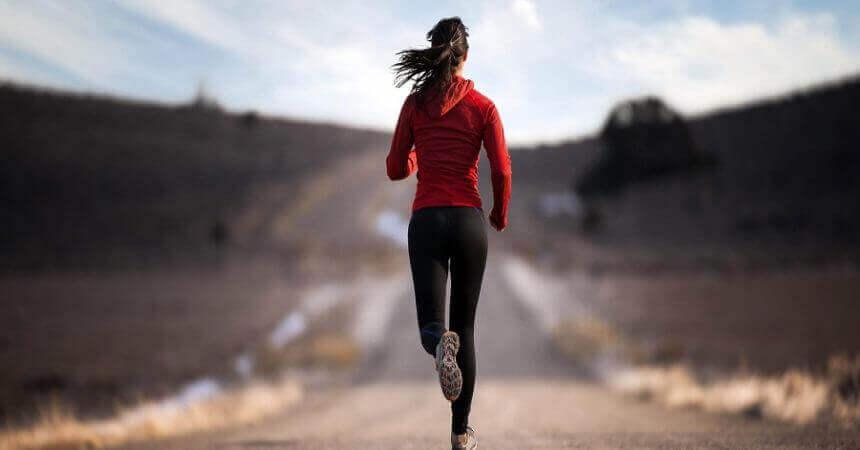 Mulher correndo em estrada