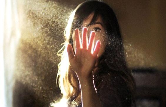 Mulher colocando a mão em feixe de luz