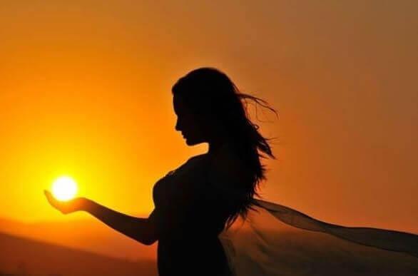 Mulher segurando o sol nas mãos