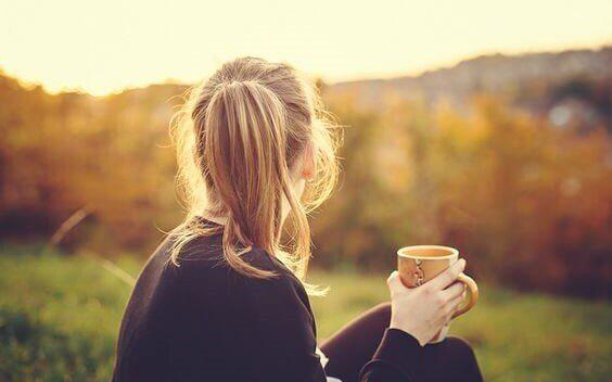 Mulher tomando um chá na natureza