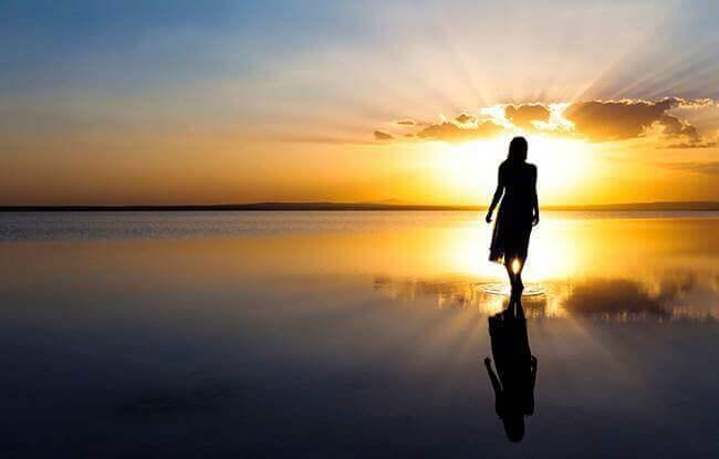 Mulher andando em praia durante o amanhecer