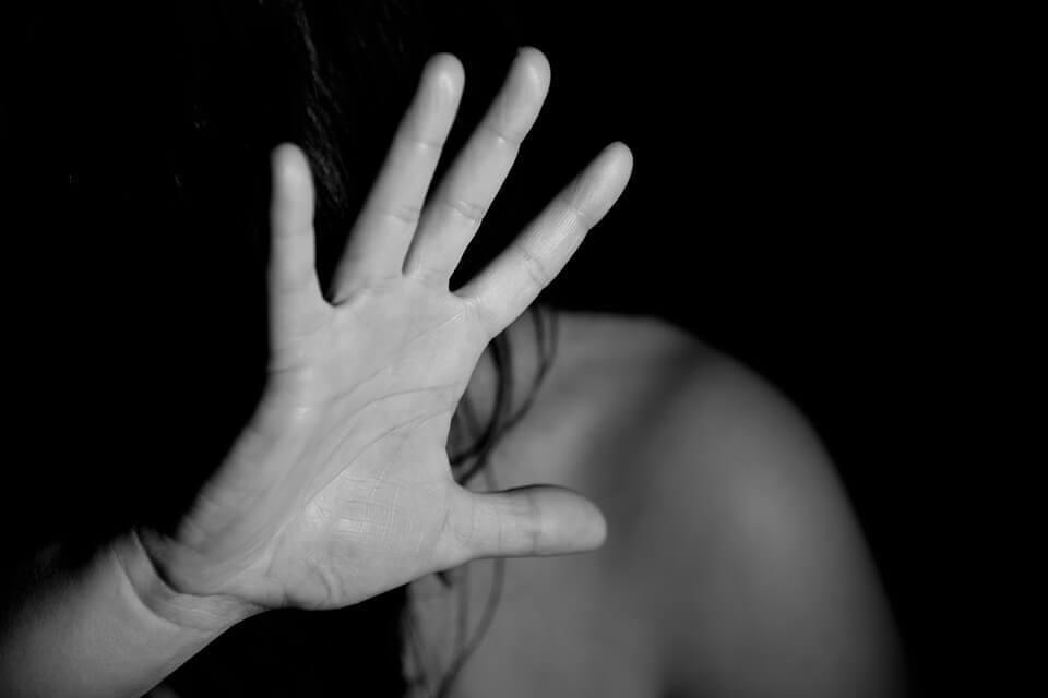 Mulher cobrindo o rosto com a mão