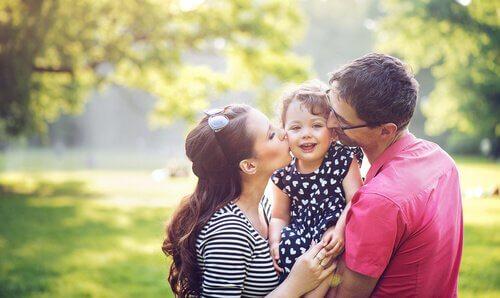 Pais beijando as bochechas da filha