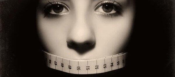 Mulher com fita métrica na boca