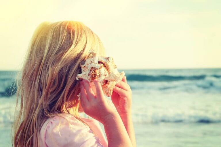 Menina ouvindo concha diante do mar