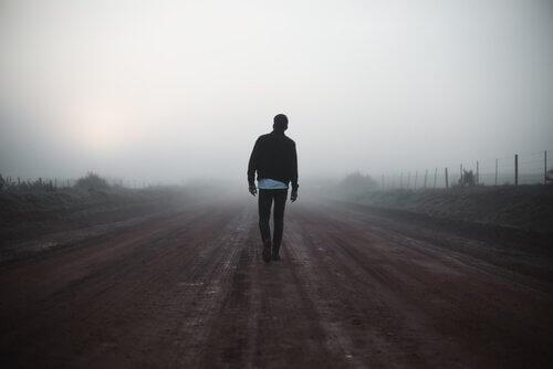 Homem andando por estrada deserta