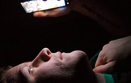 Homem olhando tela do celular deitado