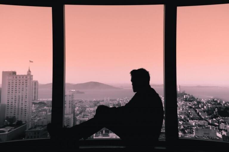 Homem olhando vista pela janela