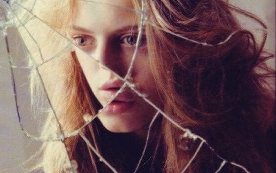 Mulher diante de espelho quebrado