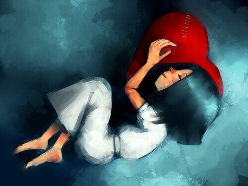 Menina dormindo usando coração como travesseiro
