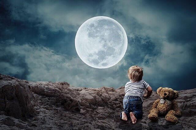 Menino pequeno diante da lua cheia