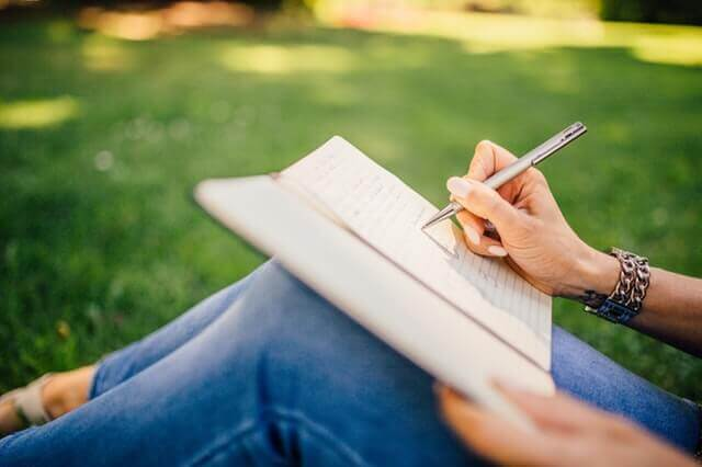 Mulher escrevendo em caderno