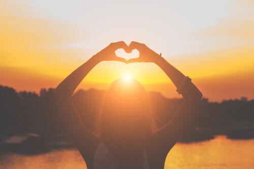 Mulher fazendo coração com as mãos diante de pôr do sol
