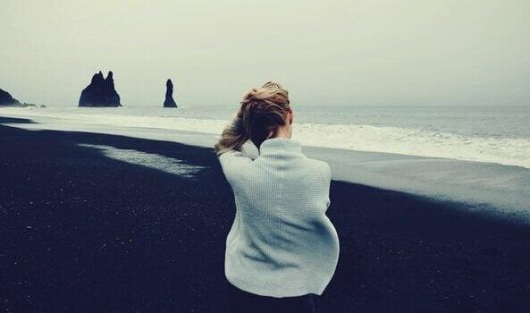 Mulher em praia de areia preta