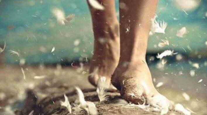 Pés caminhando com plumas voando